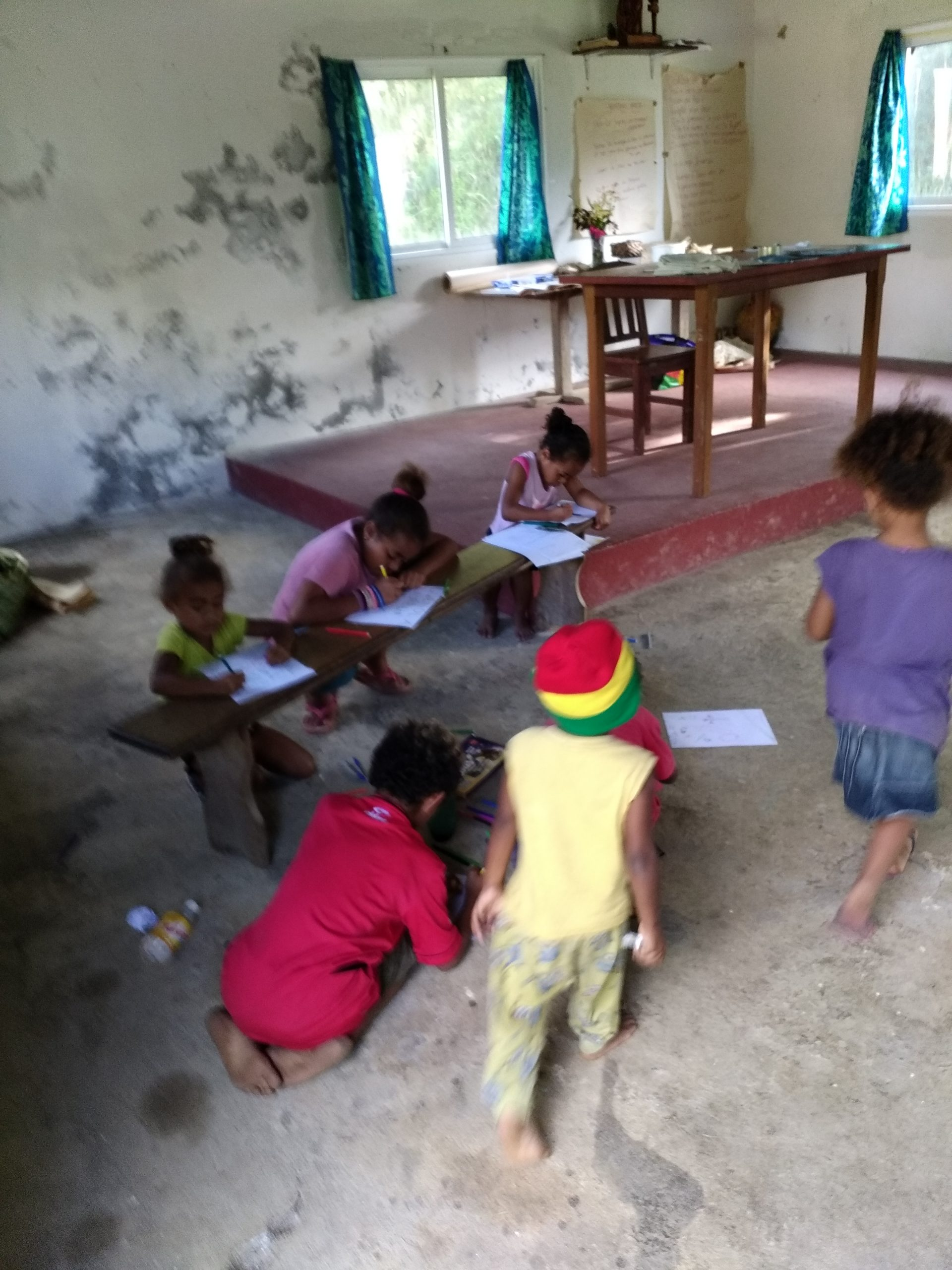 Children drawing pictures and writing the names of things in the language.