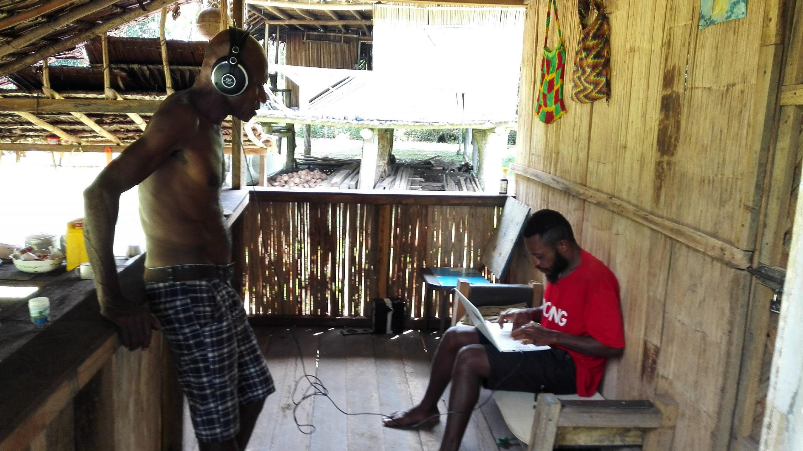 Two men in a traditional Papuan house, one wearing headphones, the other typing on a laptop.