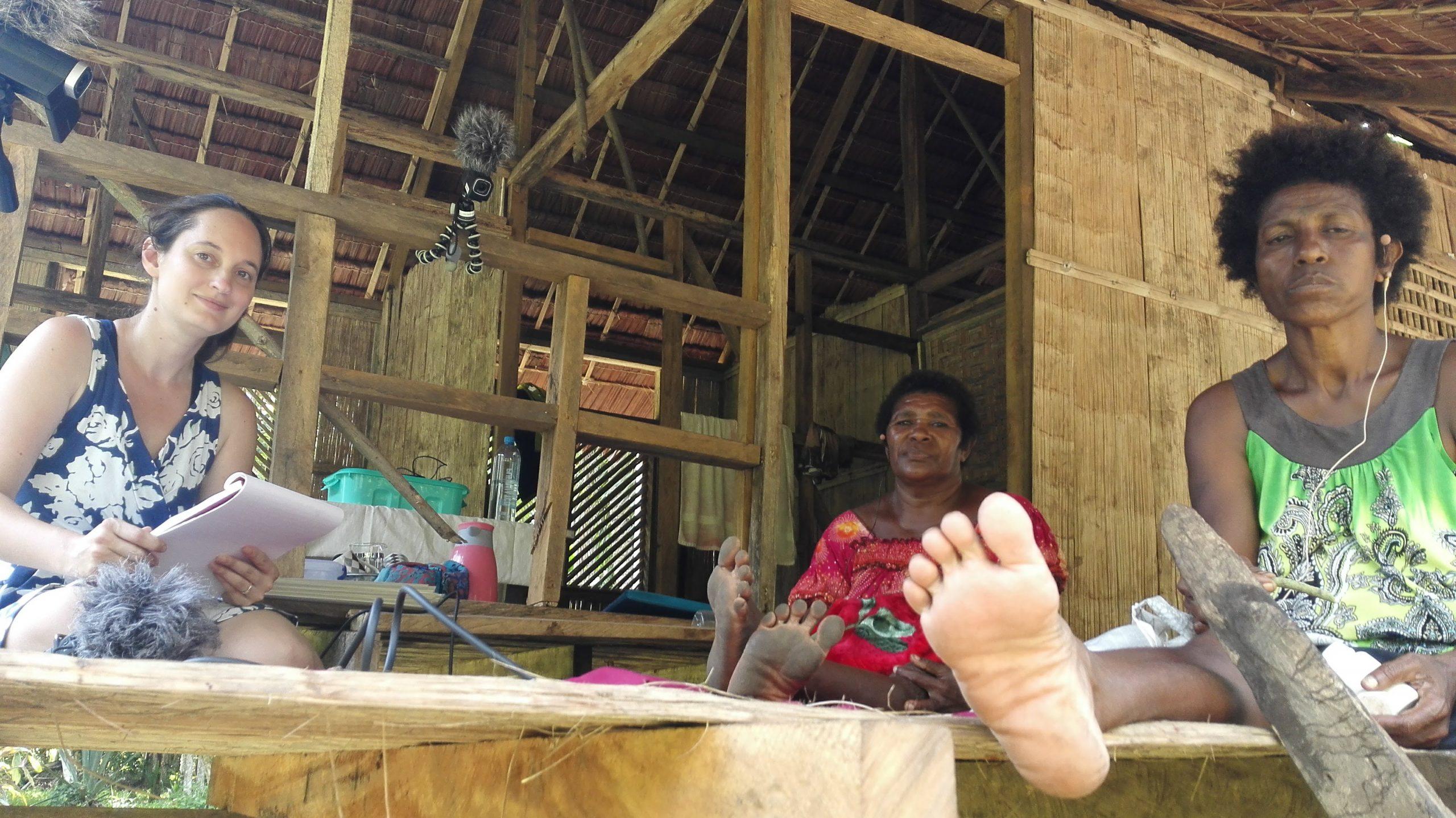 Three women sitting in in a Papuan stilt house. Danielle Barth (Left) interviews Matukar community members Rosa Kibis Dikoi (Centre) and Cathy Samun Wiliang (Right). Photo by Jillian Forepiso