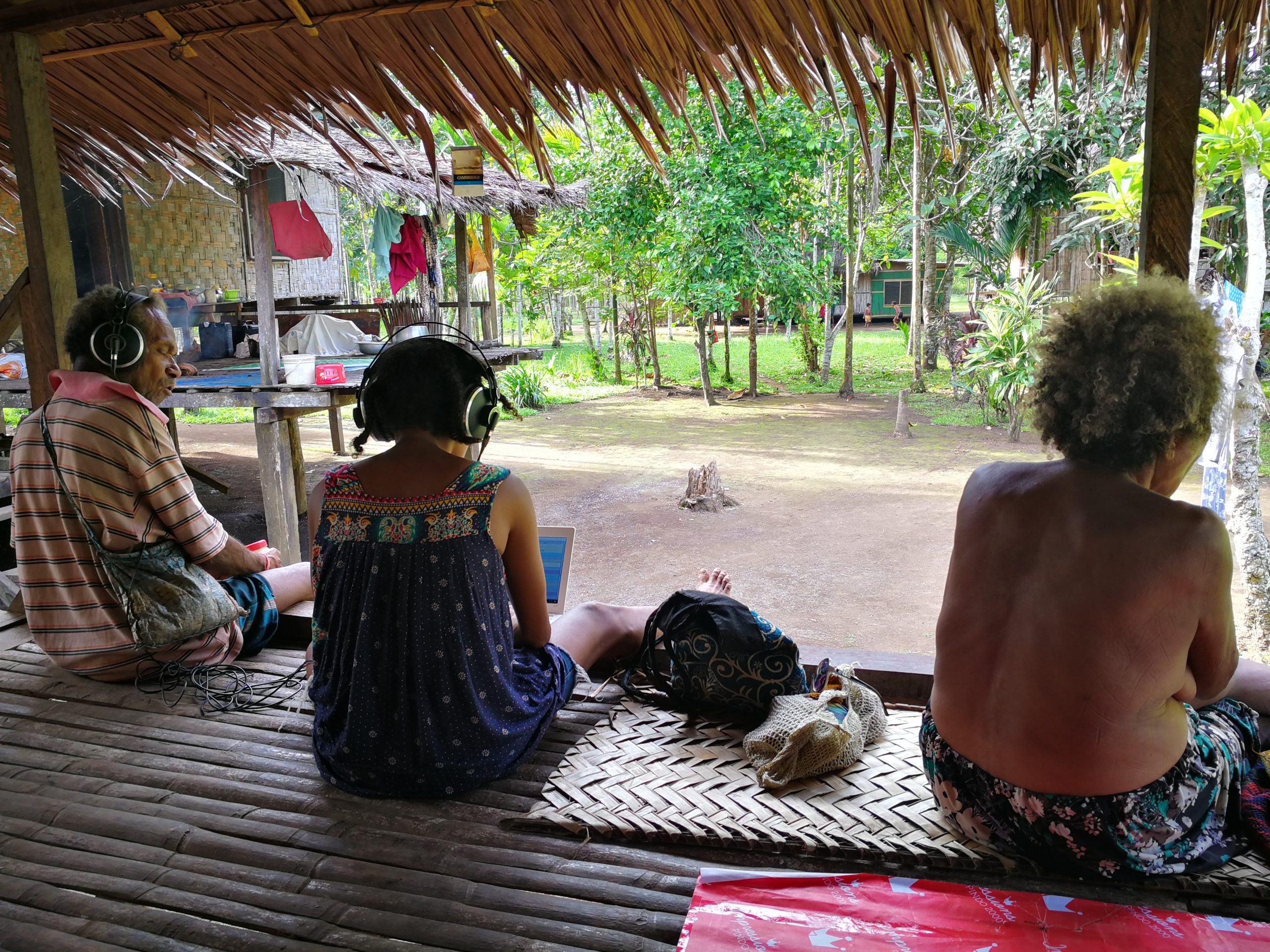 Three people sitting in a Papuan stilt house transcribing text on a laptop.