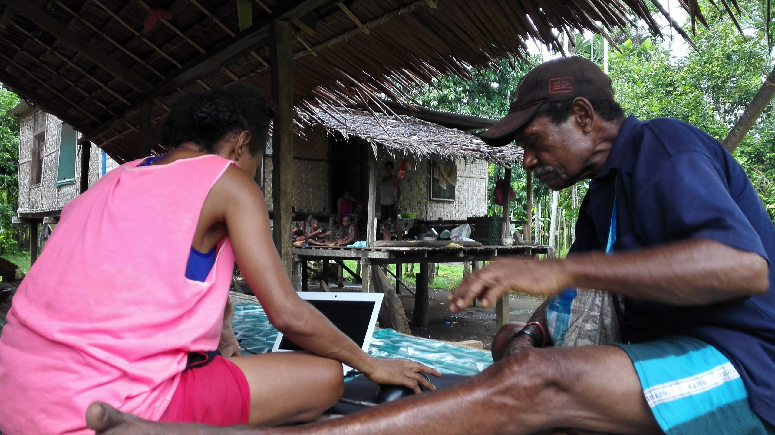 Two people and a laptop in a Papuan stilt house