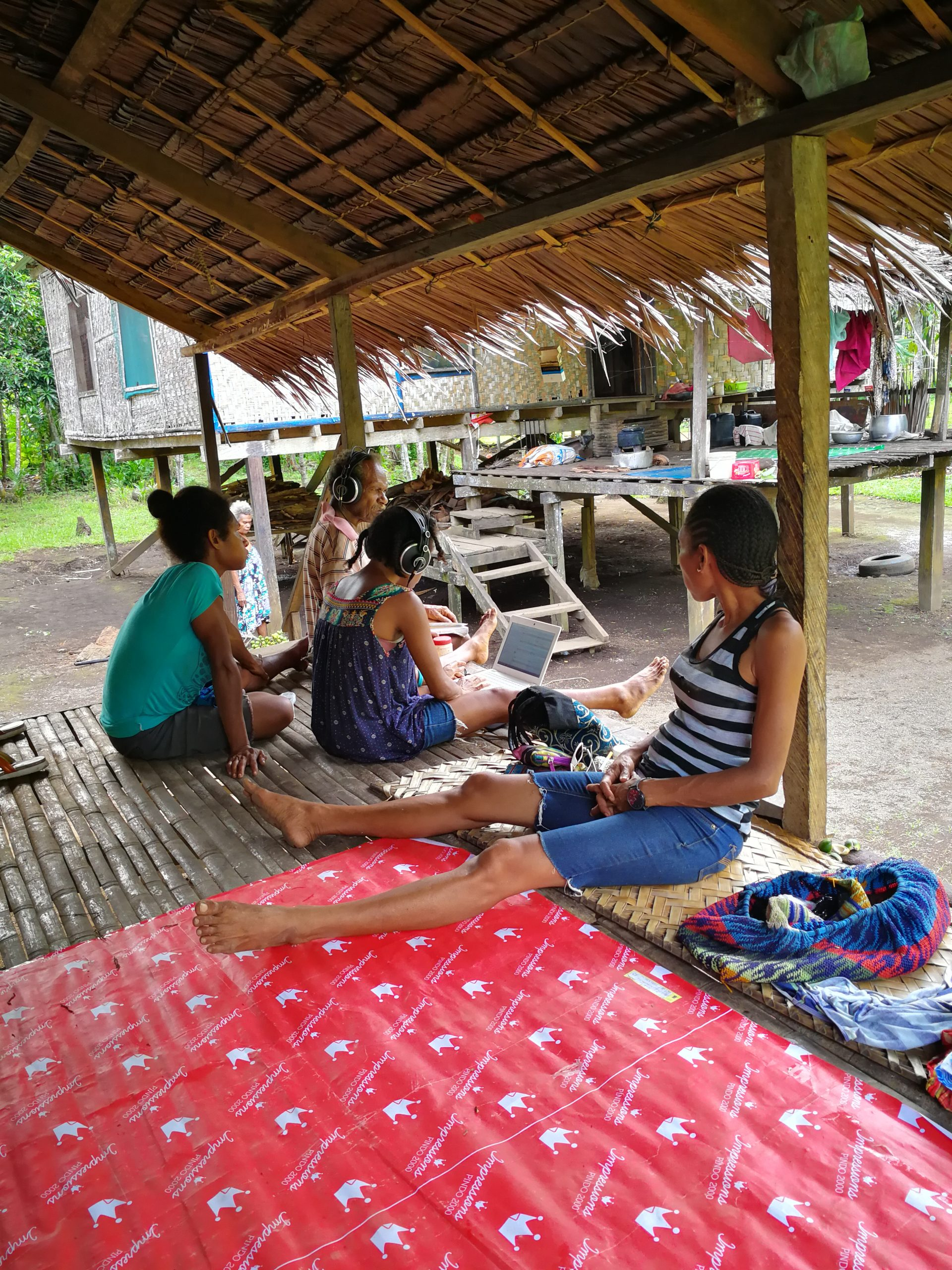 A group of people sit in a Papuan stilt house transcribing a text on a computer.
