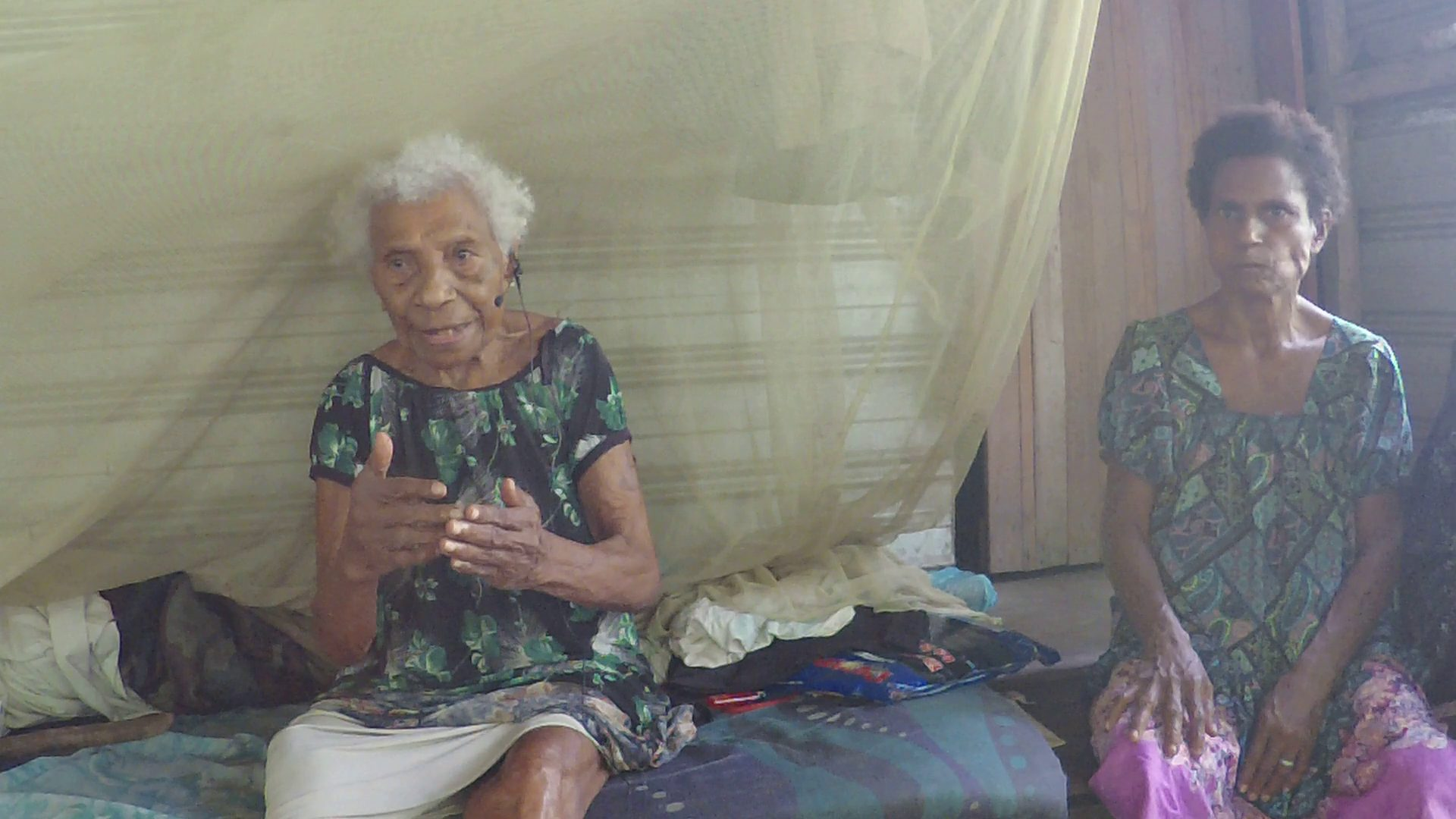 Two women. Video still of Komik Tabag talking about her time as a young woman during World War II. Next to her sits Tukan Pain Francis.